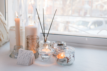 home still life in the interior with collection of candle stick and aroma stick,on the windowsill, a cozy home decor, the concept of home items, white monochrome Фото со стока