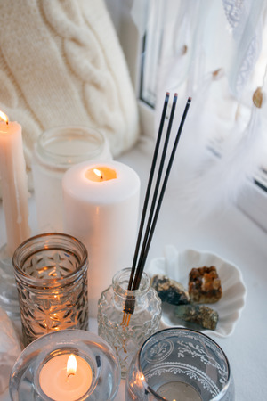 still life home atmosphere in the interior with candles and aroma stick on the windowsill, home decor elements, the concept of comfort and coziness Stock Photo