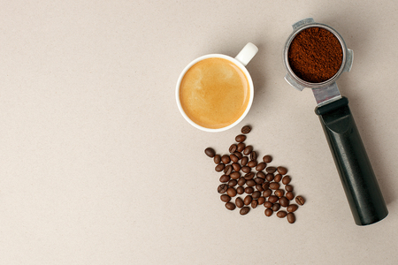 coffee in white cup, coffee beans and handle coffe machine filter on gray board from above, minimal conceptual photo, Morning coffee routine