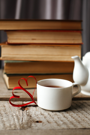 Old vintage books and cup with heart shape on wooden table, concept of leisure cozy time, hobby time to read