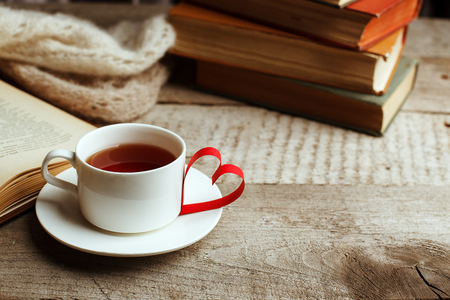 Love of books, reading. Stack of books on the wooden table.and origami paper craft the shape of a heart, cup of tea.