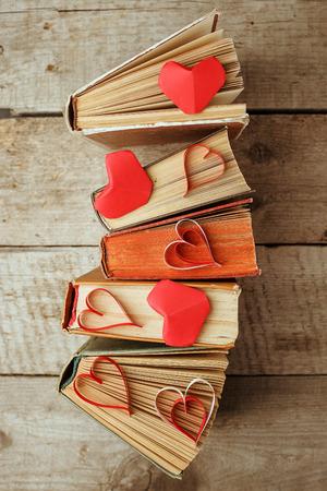 Varios libros antiguos y papel origami corazón rojo artesanal en madera vintage Foto de archivo
