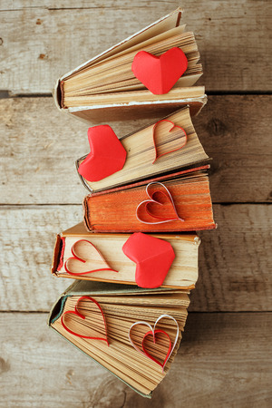 various old books and origami paper craft red heart on vintage wooden Standard-Bild
