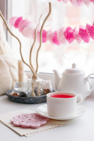Still life of used candles, tea, teapot, pillow and pink paper garland on a white table near