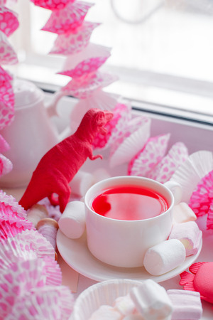 Scented herbal tea in white cup, candy pink decor, marshmallow sweets, pretty morning tea party