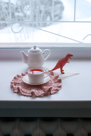 Surrealistic wonderland tea drinking - a mug with flavored pink tea, crocheted napkins, a teapot, toys - fish and dinosaur Stock fotó