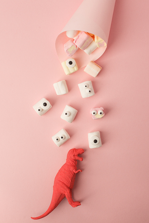 Marshmallows with funny kawaii emoji eyes in paper cone on pink