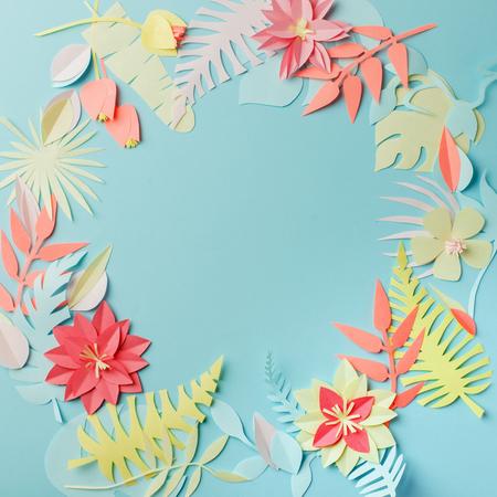 Bunte handgemachte tropische Papierblumen und Blätter auf blauem Pastellhintergrund mit Kopienraum in der Mitte, Sommerfrühlingsblumenkonzept, Papercraft-Origami-Idee