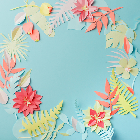 Colourful handmade tropical paper flowers and leaves on blue pastel background with copyspace in the middle, summer spring flower concept, papercraft origami idea