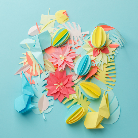 Chaos mess papercraft flowers and decor background, work in progress, paper details on pastel blue background, muted color