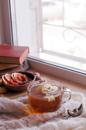 Cup of tea with apple, knit a blanket, dried fruit and books on the window sill, concept of cozy homely weekend, relax, tea party background, vertical, copy space