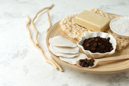 Set for anti-cellulite massage procedures. Coffee scrub, coffee grains, sea salt, soap, sponge on wooden plate and gray background, wellness homemade organic concept Foto de archivo