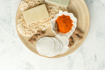 Ingredients for Face Mask with turmeric powder, spa procedures for skin health. Organic wellness treatment - curcumin powder, soap, sponge, natural massage gloves