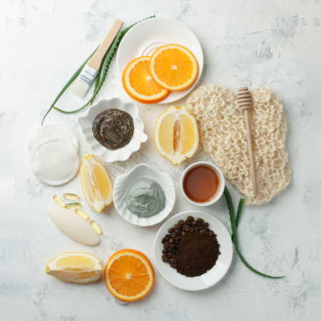 Homemade skin care and body scrubs and mask with natural ingredients aloe vera, lemon, coffee, oranges, clay, honey set up on white wooden background with flat lay