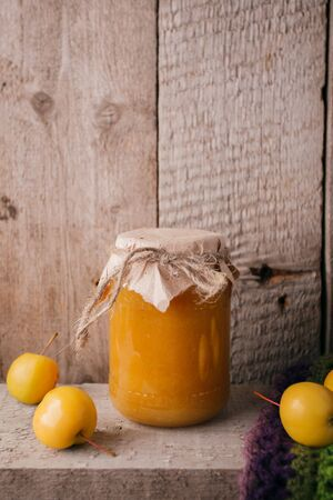 Homemade apple jelly in glass jars with fresh apples on a wooden table.