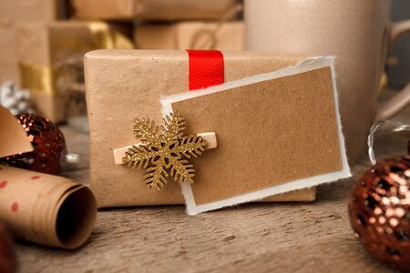 Handmade present box with tags on vintage wooden background, christmas decor closeup, copy space