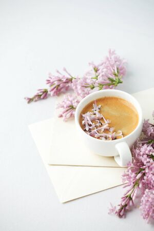 Minimalistic still life with coffee and lilac branches, envelopes on the white table, morning female concept, copy space, mother day, 8 march, saint valentine day