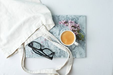 Woman desktop elegant. Coffee cup and ililac branches on marble plate on white the table. Mock-up for artwork. View from above. Flat lay. Springtime famale concept