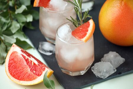 Grapefruit and rosemary gin cocktail, refreshing drink with ice, summer time, resort bar cart menu concept 免版税图像
