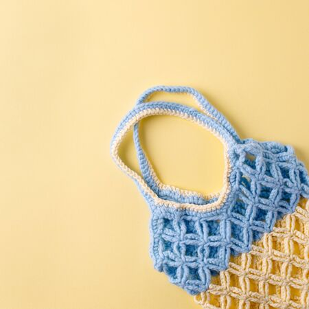 top view of empty yellow blue string bag on yellow background, zero waste eco-friendly trendy shopping minimal concept Imagens