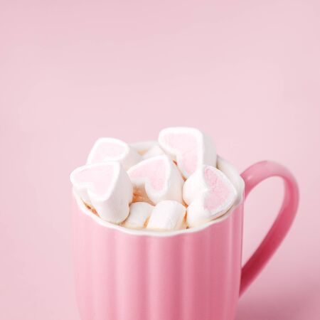 Pink light pastel background. Cup of dark coffee, hearts shaped marshmallow. Valentine's wedding day concept. Romantic girly femininy background