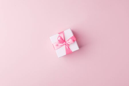 Present or gift box with pink satin bow on pink paper background, top view. Valentines day greeting card, black friday sale, congratulations concept. Flat lay style