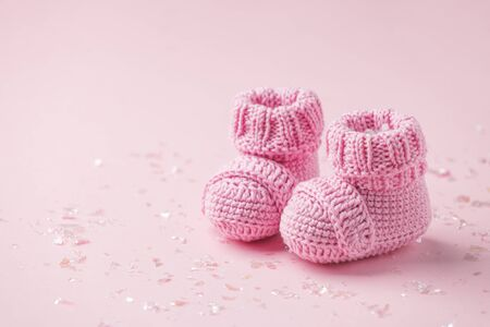 Pair of small baby socks on pink background with copy space for your warm message, baby shower, first newborn party background, copy space, cute minimal postcard