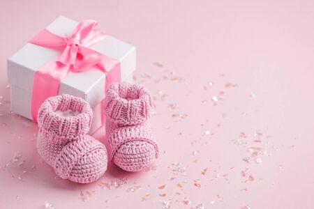 Paar kleine babysokjes en geschenkdoos op roze achtergrond met kopieerruimte voor uw warme boodschap, babydouche, eerste pasgeboren feestachtergrond, kopieerruimte Stockfoto