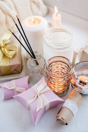 Paraffin wax candles and one tealight in a glass candle holder and aroma stick, romantic gift boxes