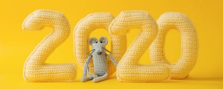 Happy New year concept. 2020 knitted yellow numbers with the symbol of the year the rat on a yellow background. Seasonal funny decoration, holiday symbol, party, banner