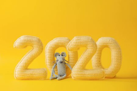 Happy New year concept. 2020 knitted yellow numbers with the symbol of the year the rat on a yellow background. Seasonal funny decoration, holiday symbol, party, monochrome