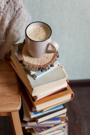 Sweet Home. Still life details in home interior of living room. Sweaters and cup of warming beverage and the books. Read, Rest. Cozy autumn fall or winter concept.