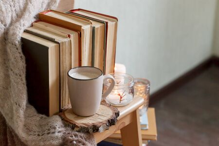 hygge and cozy home concept - books, cup of coffee or hot chocolate and candles, seasonal autumn fall winter relax time, concept of read, monochrome, copyspace