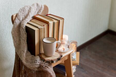 Mug with coffee and home decor on wooden chair. Warm sweater old books, candles, seasonal fall autumn winter weekend concept, copy space, relax unplag time Stock fotó