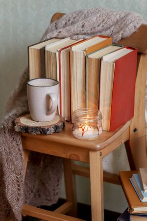 Mug with coffee and home decor on wooden chair. Warm sweater old books Stock Photo