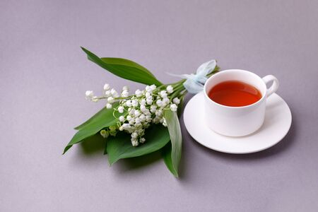 Lily of the valley flowers with green leaves ant teacup on gray background. Flower pattern. Floral background. Top view. Flat lay. Spring, summer concept. March 8, mother's day