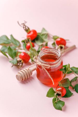 Fresh rose hip berries and honey on pink background, copy space. Ingredient for winter autumn fall seasonal hot drink, immunity alternative medicine beverage
