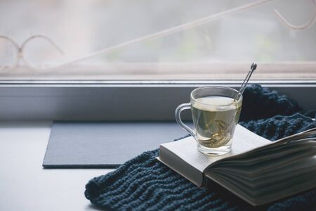 Knitted Sweater cup of hot tea Open Book on window. Cozy Winter Autumn day. Natural Light Authentic Tranquil Atmosphere. Kinfolk Hygge Slow Living Style. Matte Toned Stock Photo