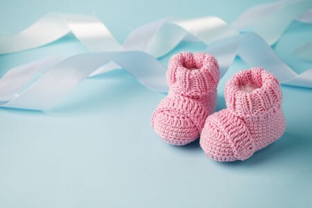 Newborn baby booties, pink, cozy and nice. Child clothe and boots - knitted and sweet. Text space, copy past and place for your design, baby shower background