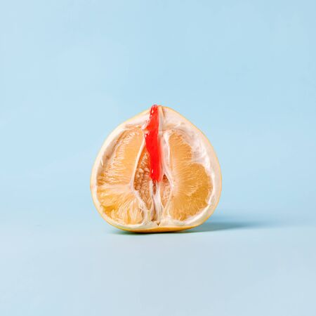 Half of pomelo citrus with honey wax red on blue background. Clitoral or vaginal orgasm. Vagina symbol. Sex, woman intimate health, depilation sugaring, menstruation minimal concept.