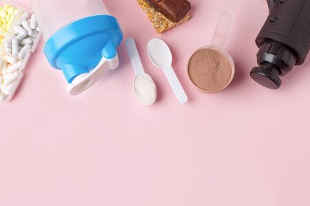 Therapeutic percussive massage gun, fit meal, pills, sport energy bar on pink Stok Fotoğraf