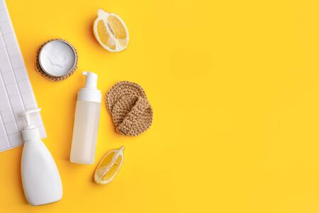 Set of eco-friendly natural cleaning products on yellow kitchen table: soda, essential oils, cellulose sponge, rags, lemon, soap, vinegar. Zero waste, eclogical habbits