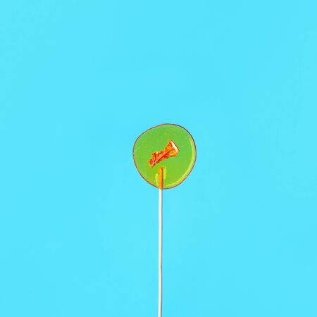 Yellow lollipop ion blue background. Girls hold hard candy caramel on stick, sweets holidays concept, copy space for text, minimal, summer creative idea - sun and blue sky Reklamní fotografie