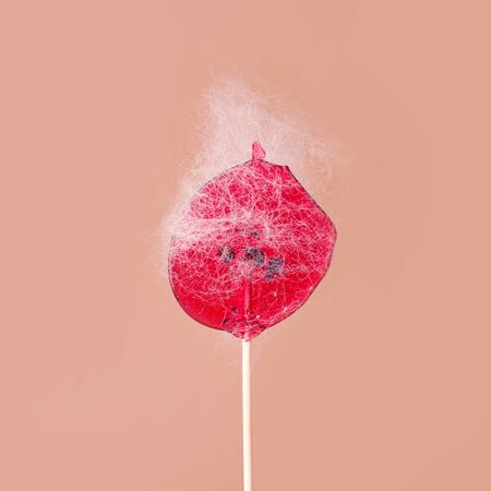 Pink lollipop with sticky hair on beige background. The concept of a beauty salon, hair removal, depilation. Sugaring, wax depilation creative idea
