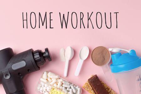 Home workout, lockdown. Therapeutic percussive massage gun, fit meal, pills, sport energy bar on pink background - concept of modern sport activity and diet, lifestyle routine, wellness, healthcare