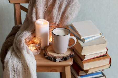 Self isolation, please stay home. Still life details in home interior of living room. Sweaters and cup of warming beverage, books. Read, Rest. Cozy autumn fall or winter concept.