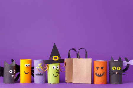 Autumn season Halloween holiday sale concept - toy from toilet roll tube? recycle idea and paper cragt shoppin bag on purple background, eco-friendly easy diy, flyer, coupon