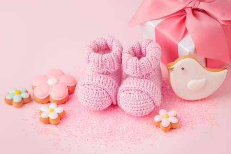 Pregnancy motherhood perenthood concept, Three pairs of baby booties on pink background, baby shower, first birthday party banner, handmade socks, daycare, kindergarten, day nursery