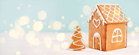 Homemade gingerbread house scene on warm blue bokeh background, Merry Christmas, Happy New Year congratulations banner, copy space, flyer, post card, voucher, coupon
