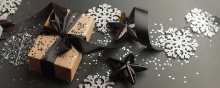 Gift or present box with black satin ribbon bow on red table top view.